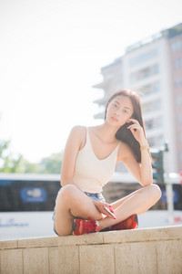 Young handsome asiatic long brown straight hair woman sitting on a small wall in city backlight, cross-legged, holding a smartphone, looking in camera, pensive - technology, thoughtful concept