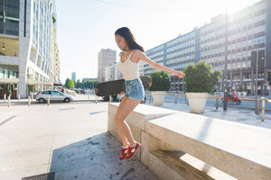 Young handsome asiatic long brown straight hair woman skater jumping down from a small wall, listening music with earphones, overlooking right - sportive, music, technology concept