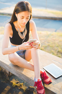 Young handsome asiatic long hair woman sitting on small wall, listening music with earphones, using smartphone looking down the screen, and tablet - technology, multitasking, social network concept