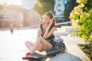 Young handsome asiatic long hair woman skater sitting on a small wall in the city backlight, listening music with headphones, holding a smartphone, looking down the screen - technology, relax concept