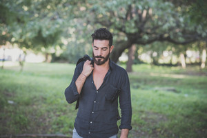 young handsome attractive bearded model man in the woods