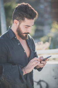 young handsome attractive bearded model man using smartphone in urban context