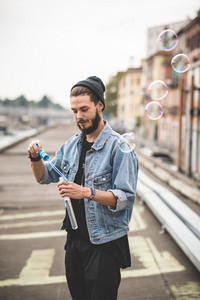 young handsome bearded hipster man blowing bubbles soap in the city