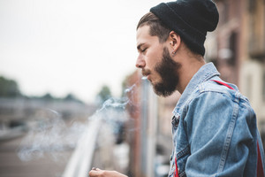 young handsome bearded hipster man smoking cigarette in the city