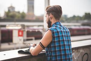 スマートフォンを使用して市内でイヤホンで音楽を聴く若いハンサムなひげのあるヒップスターマン