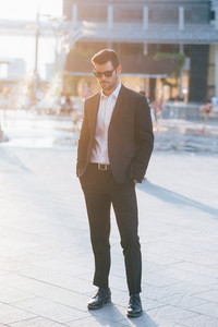 young handsome black hair modern businessman posing in the city backlight, looking downward - successful, business, working concept