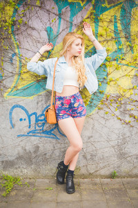 Young handsome blonde caucasian fashion girl posing leaning on a wall in the city suburbs