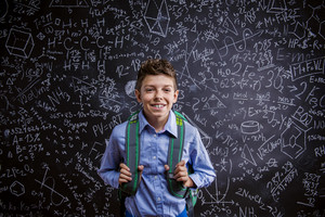 Young handsome boy with school bag in front of big blackboard