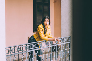 young handsome brown straight hair woman leaning on handrail outdoor in the city using smart phone hand hold looking at camera pensive - technology, communication, social network concept