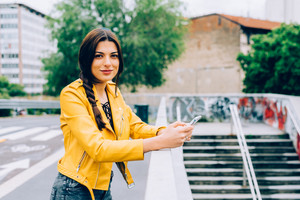 young handsome brown straight hair woman leaning on handrail outdoor in the city using smart phone hand hold - technology, communication, social network concept