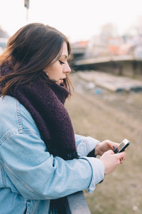 Young handsome brunette caucasian girl using a smartphone connected online in a park in the city. tecnology, connectivity, e-commerce- business, social network concepts