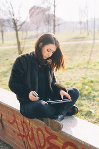 Young handsome brunette caucasian girl using a tablet an a smartphone connected online in a park in the city. tecnology, connectivity, e-commerce- business, social network concepts