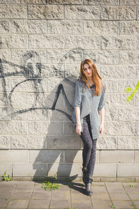 Young handsome brunette eastern fashion girl posing leaning against a wall in the city suburbs, right leg flexed, looking in camera - wearing gray jeans, black and white striped shirt