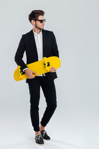 Young handsome businessman in suit and suglasses holding yellow skateboard over gray background