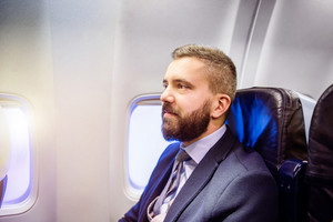 Young handsome businessman sitting inside an airplane
