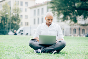 Young handsome caucasian bald business man sitting in a city park using a laptop leaning on his knees, looking downward the screen, pensive - working, thoughtful, busy concept