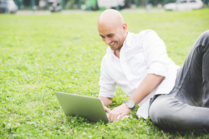 Young handsome caucasian bald business man sitting in a city park using a laptop looking down the screen laughing - working, happiness, busy concept