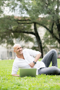 Young handsome caucasian bald business man sitting in a city park using a laptop, overlooking left, laughing - working, happiness, busy concept