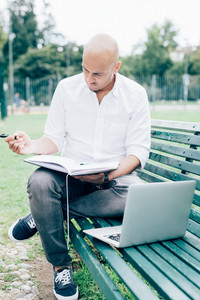 Young handsome caucasian bald business man sitting ona  bench in a city park using a laptop and writing on a agenda  looking down, pensive - working, thoughtful, busy concept