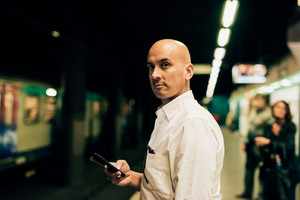 Young handsome caucasian bald business man standing on the underground platform, overlooking left waiting the tube holding a smartphone- work, waiting concept