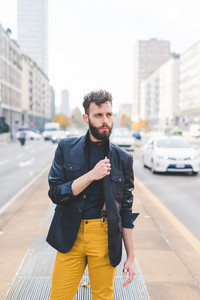 young handsome caucasian bearded businessman posing outdoor in the street, looking over pensive wearing glasses - business, thoughtful, serious concept
