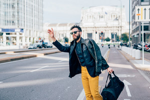 Young handsome caucasian bearded contemporary businessman outdoor in the city, holding a bag and looking for a taxi - technology, communication, transport concept