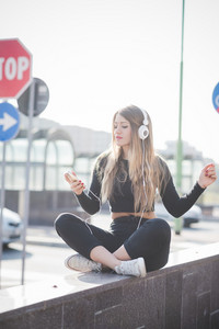 young handsome caucasian blonde hair woman sitting on small wall in city, listening music with headphones and smartphone handhold, looking downward tapping screen - music, relax, technology concept