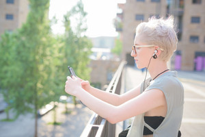 young handsome caucasian blonde italian designer leaning on a handrail, listening music with smartphone and earphones, looking the screen - technology, social network, relaxing concept
