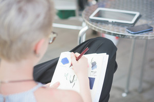 young handsome caucasian blonde italian designer sitting in a bar, drawing on her sketchbook, using tablet and smartphone too - technology, creativity, working concept - close up on the hand drawing