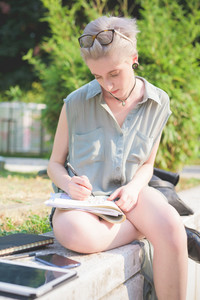 Young handsome caucasian blonde italian designer sitting on a small wall, using smartphone and tablet and sketching on a notebook - creativity, enlightenment, working concept