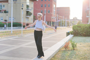 young handsome caucasian blonde italian designer walking on a small wall, trying to balance, arms wide open, looking downward - wearing striped shirt and black pants - backlight