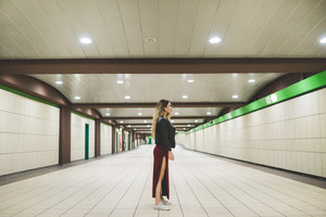 young handsome caucasian blonde straight hair woman model outdoor in the city posing in a underground station, profile view, wearing black leather jacket and long red skirt