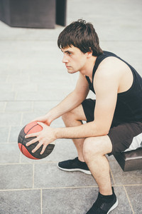 Young handsome caucasian brown hai sportive man sitting on a bench holding a basket ball, relaxing after training, overlooking right - sportive, fitness, healthy, training concept