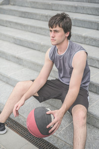 Young handsome caucasian brown hai sportive man sitting on a staircase holding a basket ball, relaxing after training, overlooking right - sportive, fitness, healthy, training concept