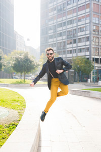 Young handsome caucasian brown hair bearded man jumping from a small wall, looking over - happiness, success, fun concept