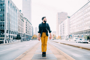 Young handsome caucasian brown hair bearded man jumping outdoor in the city, looking over - happiness, success, fun concept