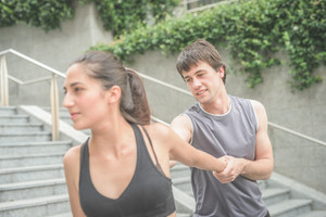 Young handsome caucasian brown hair man helping her beautiful friend to stretch, holding her arm, overlooking right - sportive, fitness, healthy concept