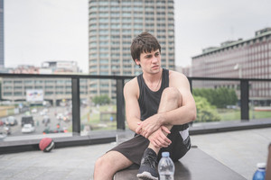 Young handsome caucasian brown hair man sitting on a bech, overlooking left, relaxing himself after training - sportive, healthy, relaxing, fitness training