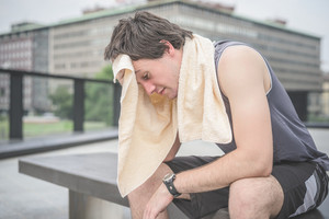 Young handsome caucasian brown hair sportive man drying himself with a towel around his neck after training, sitting on a bench, overlooking right - sportive, relaxing, training, healthy concept