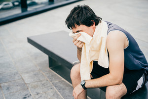 Young handsome caucasian brown hair sportive man drying himself with a towel arounf his neck after training, sitting on a bench, overlooking right - sportive, relaxing, training, healthy concept