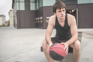 Young handsome caucasian brown hair sportive man sitting on a bench holding a basket ball, relaxing after training, overlooking right - sportive, fitness, healthy, training concept