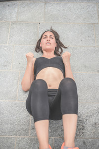 Young handsome caucasian brown hair sportive woman doing abdominal lifting her legs, fists closed, under strain - sportive, fitness, healthy, training concept