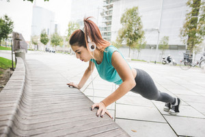 Young handsome caucasian brown hair sportive woman doing push up on a bench in a city park listening music- practice, training, fitness, sportive, healthy concept