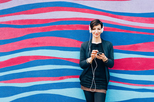 Young handsome caucasian brown hair woman leaning against a wall, listening music with headphonesand smart phone hand hold - serene, enjoying, music concept