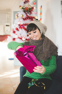 Young handsome caucasian brown short hair woman sitting on the sofa in her apartment, unwrapping a christmas present - gift, surprise, christmas concept
