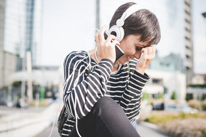 Young handsome caucasian brown straight hair woman listening music with headphones holding a smartphone, looking downward, smiling - music, happiness, carefreeness concept
