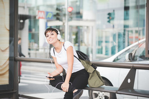 young handsome caucasian brown straight hair woman sitting on a bench at bus stop, listening music with headphones, overlooking right, smartphone handheld - technology, social network, music concept