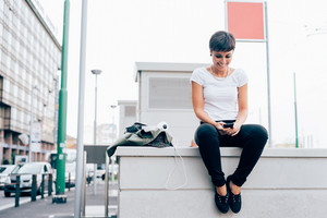 young handsome caucasian brown straight hair woman sitting on a small wall, holding a smartphone, looking down the screen, smiling - technology, social network, communication concept
