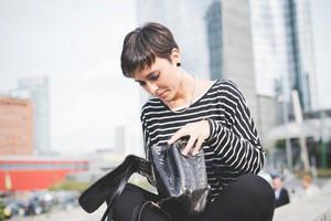 young handsome caucasian brown straight hair woman  sitting on a small wall, looking downward, searching something in her bag