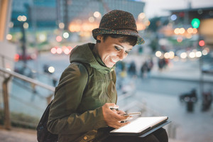 Young handsome caucasian brown straight hair woman sitting on a staircase at nightfall, tablet on her knee, smartphone handheld, face enlightened by the light of the screen, smiling -